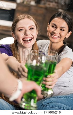 Happy young women clinking glasses with green beer while celebrating St Patricks Day
