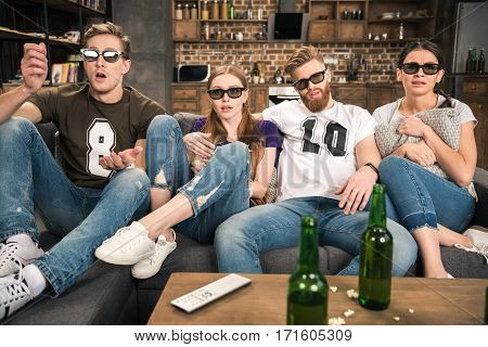shocked young friends in 3D glasses watching movie at home