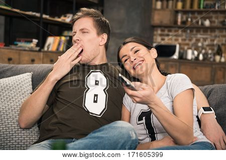 bored yawning man and smiling woman sitting on sofa and watching movie
