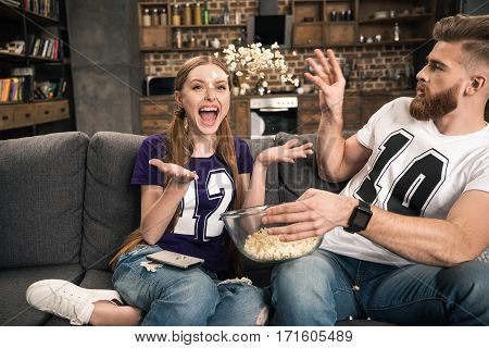 Portrait of excited couple throwing popcorn while watching movie at home