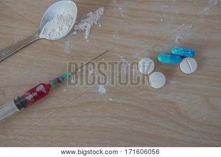 syringe and blood, Drug and  spoon cooked heroin on a wooden background. in the studio.