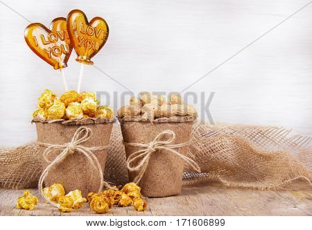 Paper bucket of caramel popcorn and peanuts. Two lollipop in the shape of a heart. Set to view the movie
