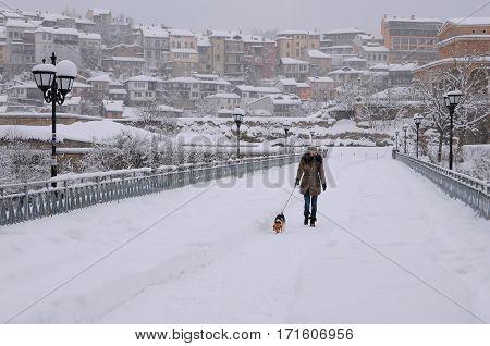 VELIKO TARNOVO BULGARIA - JANUARY 19 2017: Woman with the dog walks along the snowy bridge