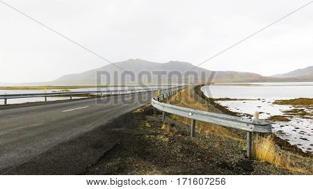 A vanishing road across a lake in Iceland
