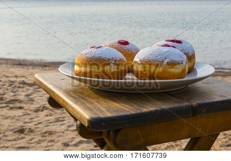 Festive sweet donuts are traditional symbols of Hanukkah holiday. Selective focus with water background