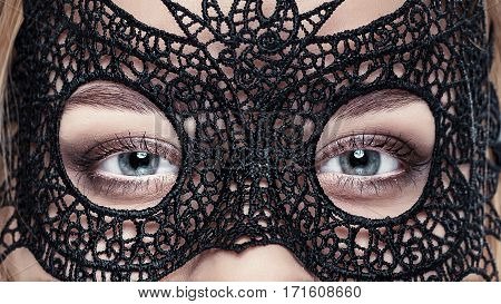 closeup of beautiful sensual woman with green eyes in black lace mask. look in venetian mask