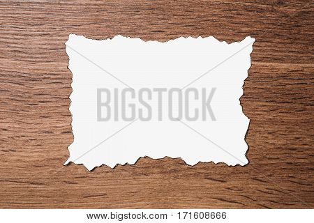 White sheet of paper scorched by fire on a brown wooden background. Layout.