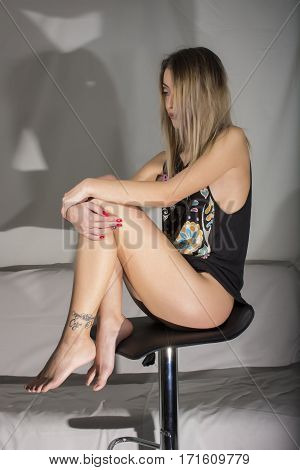 Blond girl with black top  sitting on chair