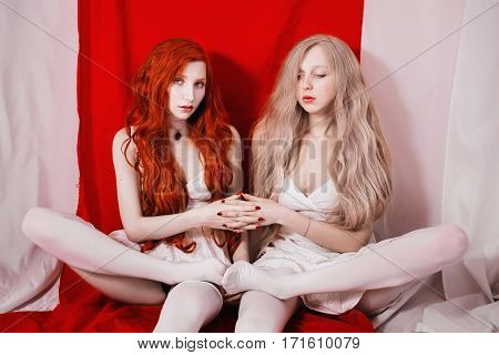 Red-haired girl and a blonde on a red white background. Two lesbian women. Fetish model.