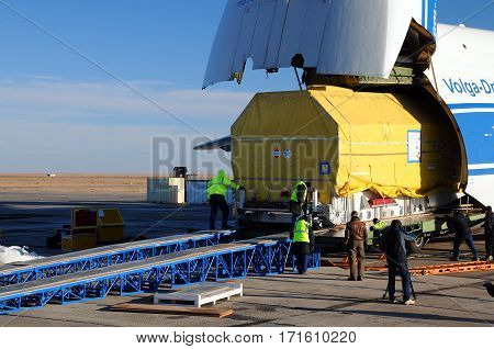 BAIKONUR KAZAKHSTAN - NOVEMBER 11 2013. Russian Volga-Dnepr Antonov AN-124 long-range heavy transport plane is being unloaded in Yubileiny airport
