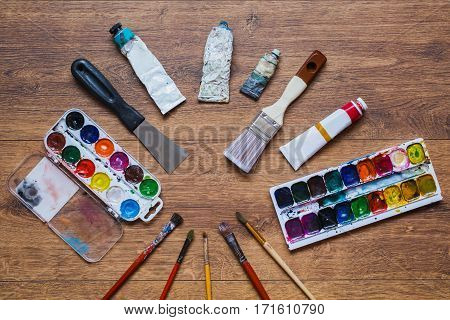 Artistic squirrel brushes tubes of oil paints and watercolors on a wooden background. Used tools for artists and schoolchildren. Tools for art.