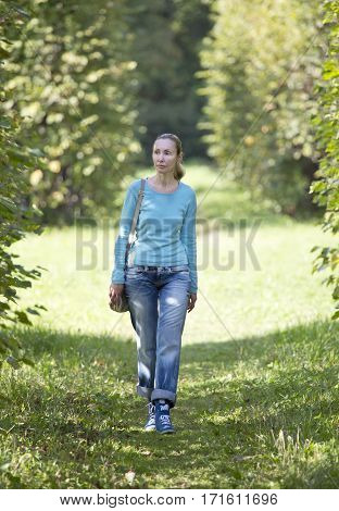 The young woman in a blue jacket walks in summer park.