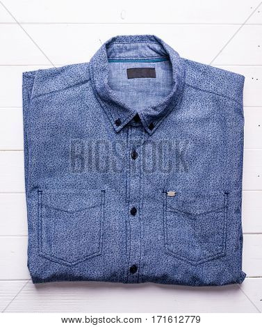carefully folded denim shirt on wooden table, top view