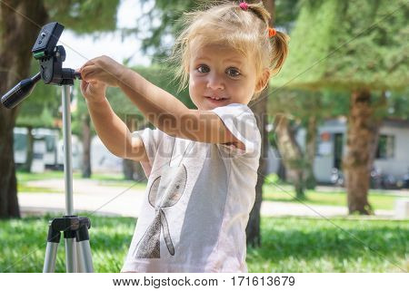 Little Photographer with Professional Tripod girl playing outdoors.