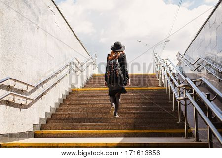 Girl in a hat with red hair rises from the underpass. A woman comes out of the subway. Man climbs the stairs.
