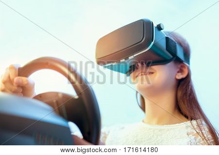 Happy girls in virtual reality glasses playing video game with racing wheels at home