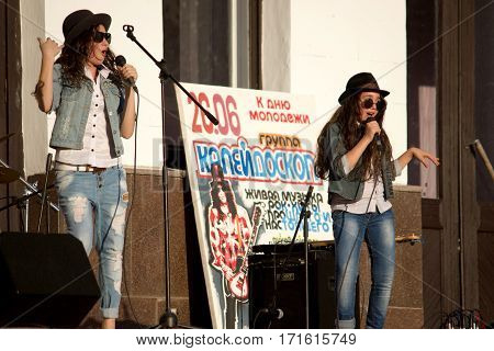 MARGANETS, UKRAINE - JUNE 26: Two young teenager girls singing on improvised enlightened stage giving concert in Marganets on National Youth Day on June 26, 2016