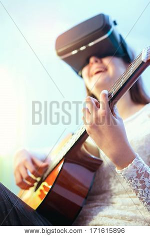 Happy girls in virtual reality glasses playing guitar at home