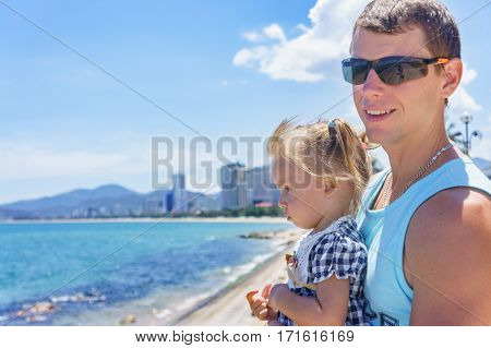 Dad and daughter playing on the promenade by the sea. young man and little girl.