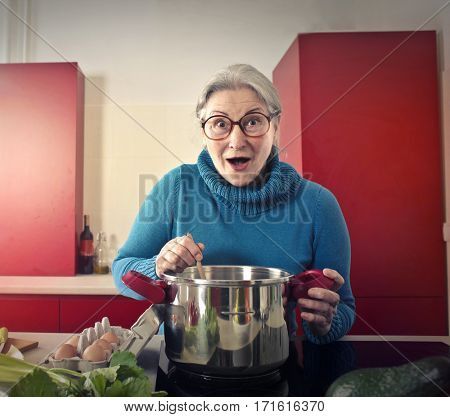 Old lady cooking surprisedly in nice kitchen