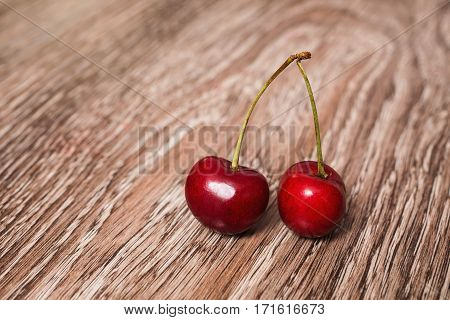 Two berries of a ripe juicy red cherry on wooden background. Red summer berries are rich in vitamins.