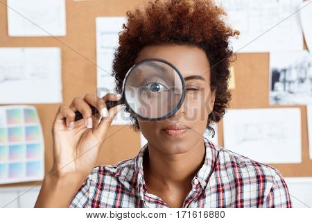 Young beautiful african worker holding magnifier infront of eye.