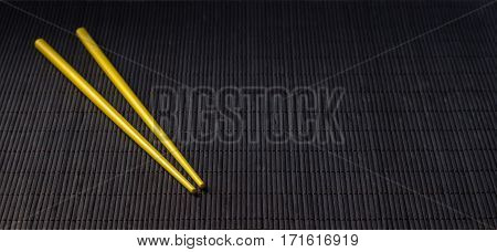 Yellow sushi chopsticks on black bamboo straw mat space for text