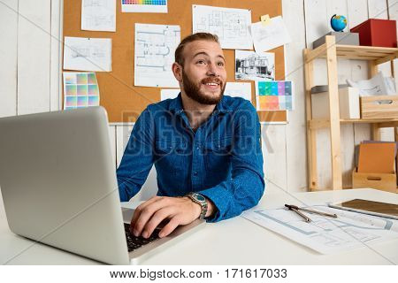 Young successful businessman smiling, sitting at workplace with laptop.