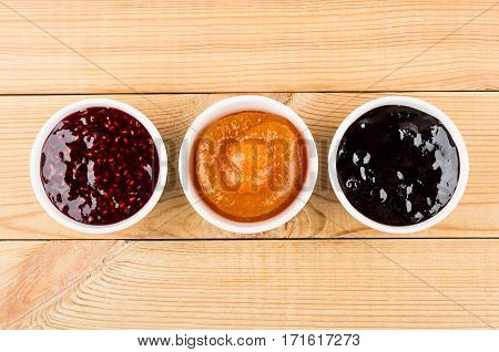 Row Of Bowls With Raspberry, Peach, Blueberry Jam On Table