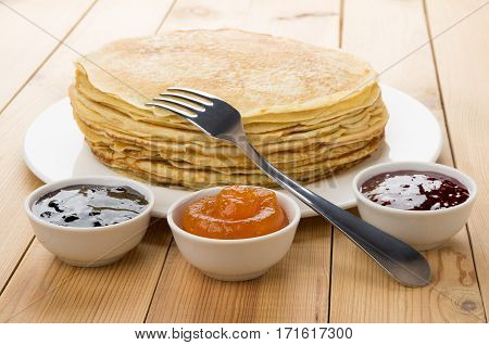 Russian Pancakes In Glass Dish And Raspberry, Peach, Blueberry Jam
