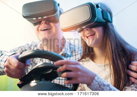 Father and daughter in virtual reality glasses playing video game with racing wheels at home