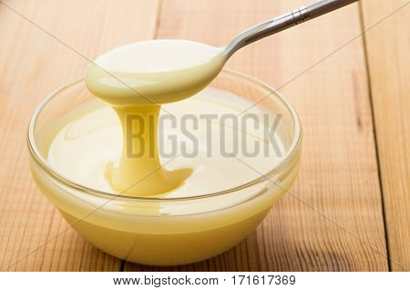 Transparent Bowl With Condensed Milk And Teaspoon On Table