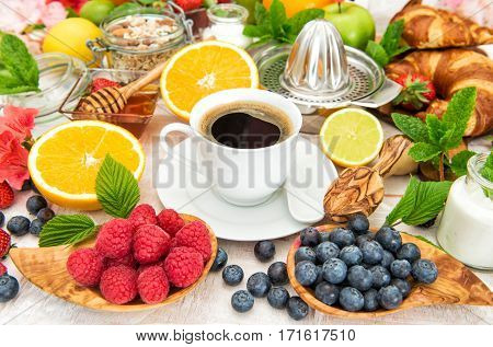 Breakfast with coffee croissants muesli fresh fruits berries orange apple milk. Healthy food concept