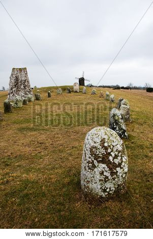 Gravefield with a stone ship and an old wooden windmill at the Swedish island Oland in the Baltic Sea