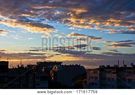 Colorful and picturesque golden clouds over city roofs at sunset in Belgrade, Serbia