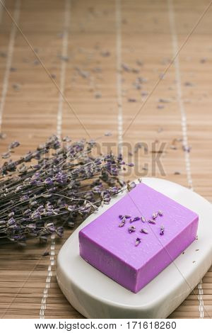 Bar of natural lavender soap on white ceramic soap dish over beige bamboo mat background