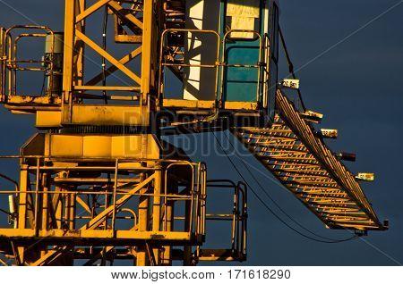 Big yellow construction crane against dark blue sky after rain in Belgrade, Serbia