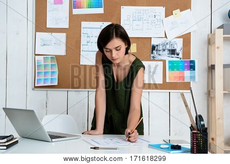 Young beautiful businesswoman working with drawings at workplace in office.