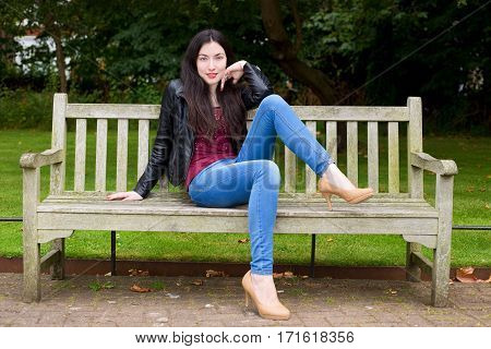 young woman sitting on a park bench posing