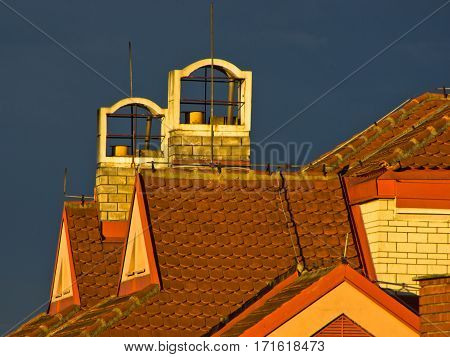 Sunlight on a building roof against dark blue sky after rain in Belgrade, Serbia