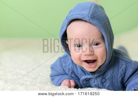 Little Boy In Blue Knitted Cardigan Lying On Stomach And Looking At Camera