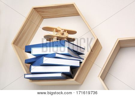 Stack of books on wooden shelf against light wall