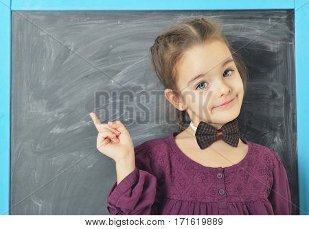 Cute little girl standing near blackboard, smiling and pointing at board. Beautiful schoolgirl. Smart pupil girl in classroom, image toned.