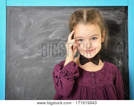 Cute little girl standing near blackboard and happy smiling. Beautiful schoolgirl. Smart pupil girl in classroom. Have Idea! Image toned.