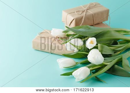 Compliment gift with spring white tulips on table