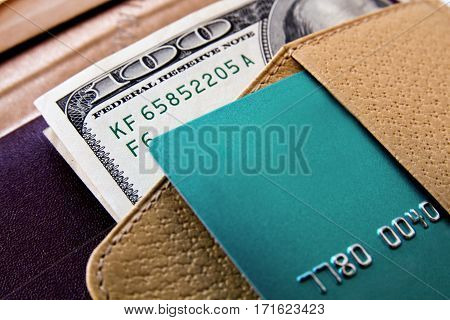 One hundred dollars bills and credit card in beige leather pocket close-up view.