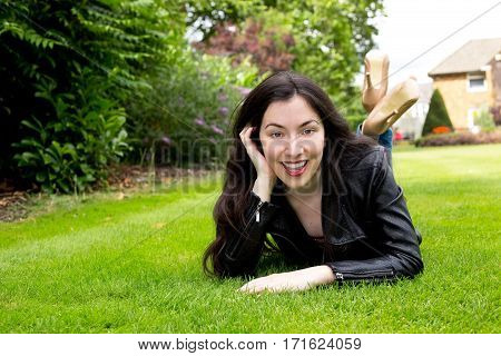happy young woman lying in the park