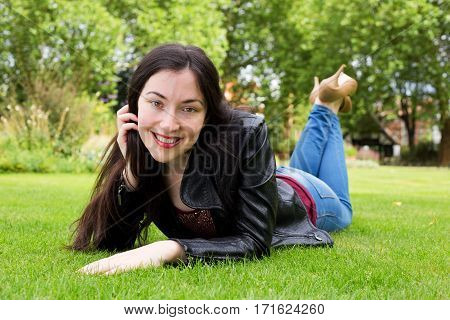 Happy girl in the park lying on the grass