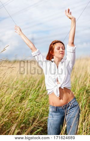 Relaxed redhead woman spending time outdoors summertime