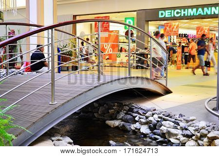 CLUJ-NAPOCA ROMANIA - JULY 28 2012: Small walkover bridge over an indoor stream in the Vivo! shopping center (formerly Polus) leading to a Deichmann store a German shoe and sportswear retail chain.